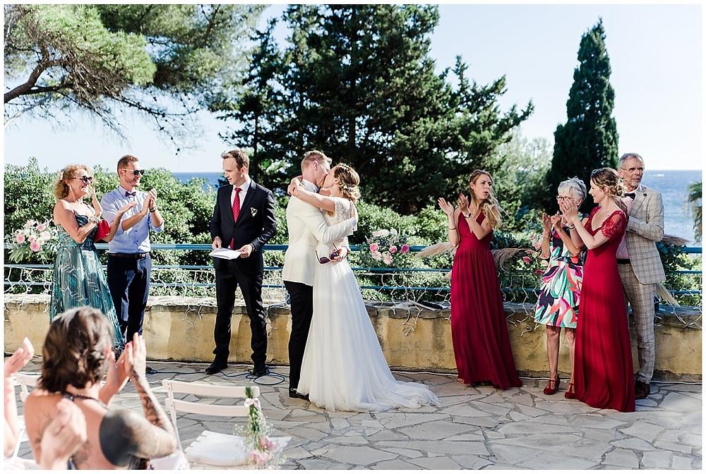 Vue d'ensemble des mariés qui s'embrassent suite à leur échange de vœux pendant la cérémonie laïque de mariage. Les témoins et invités applaudissent.