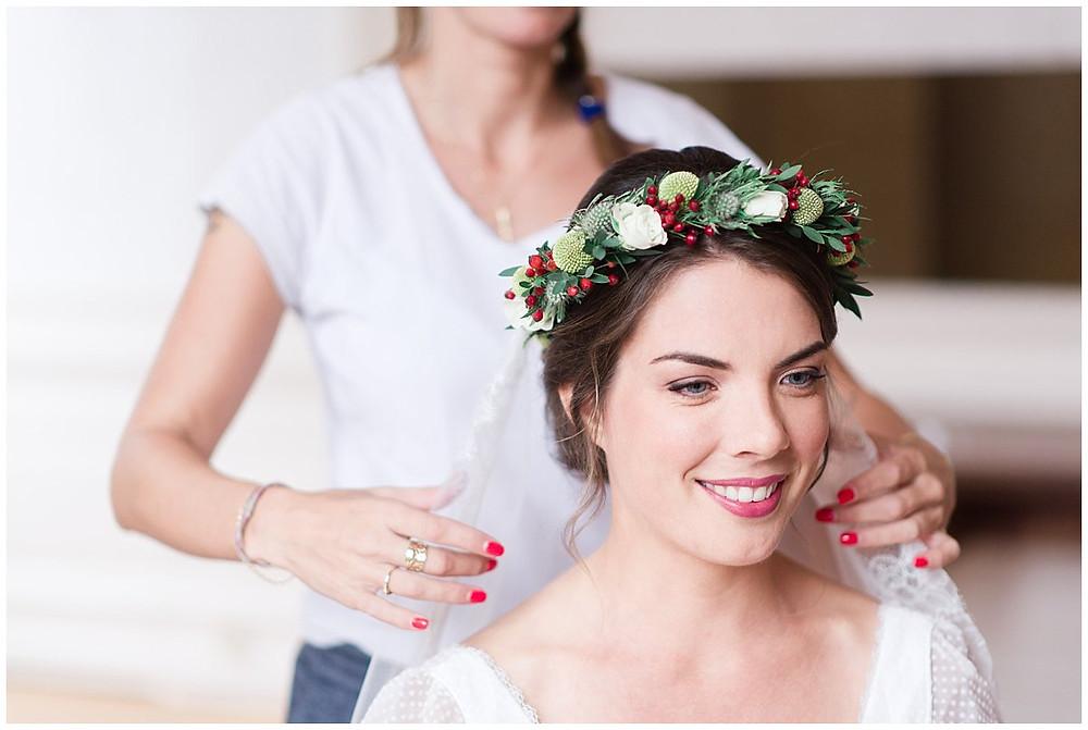 Sur cette image, on peut voir le portrait d'une mariée pendant ses préparatifs. La coiffeuse est en train de placer son voile de mariée. La mariée sourit, elle porte une couronne de fleurs.
