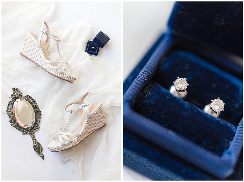 Photo des accessoires de la mariée : la bague de fiançailles dans une boite en velours bleue, les chaussures à talon compensé, les boucles d'oreilles en diamant.