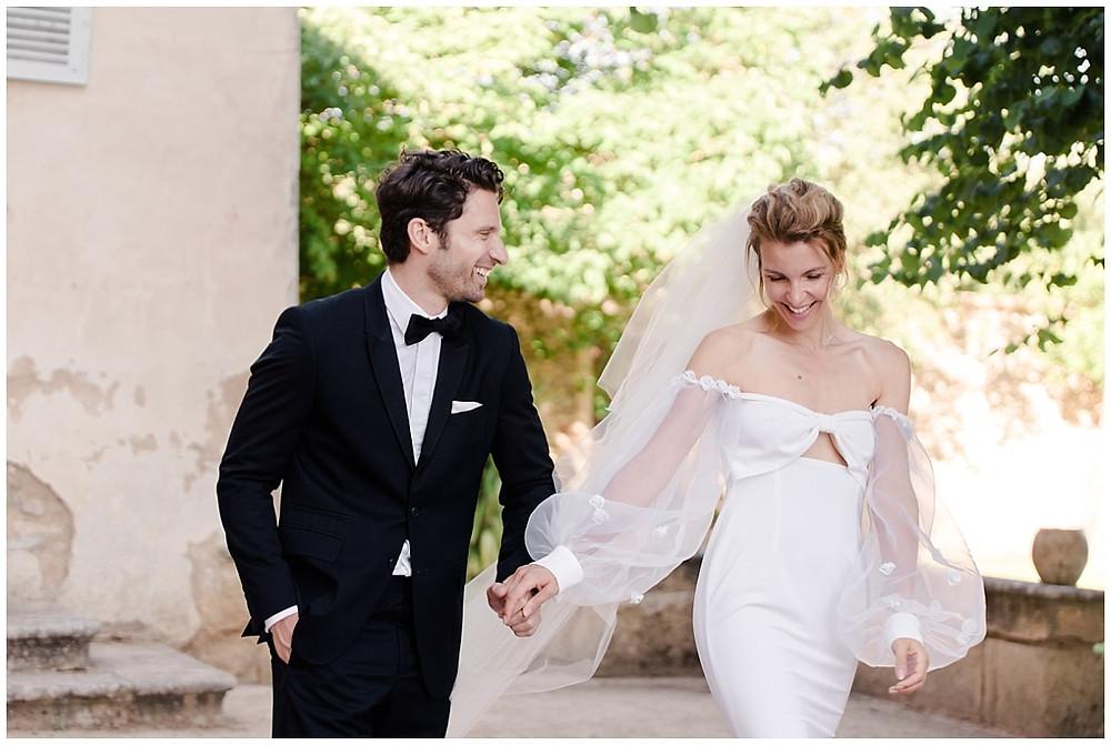 les mariés marchent dans le parc du château de Sénéguier en Provence