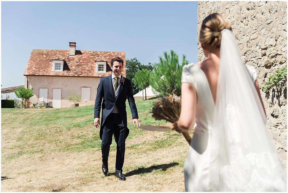 Voici le moment tant attendu de la découverte des futurs mariés : ils se découvrent pour la toute première fois dans leurs tenues de mariés. Le marié porte un costume queue de pie bleu marine, avec un gilet gris et une cravate verte. La mariée porte une robe longue blanche et fluide, ainsi qu'un chignon et un voile.