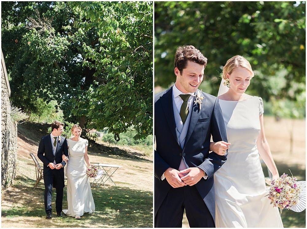 Les mariés marchent en se tenant le bras. Ils sont dans le jardin d'une propriété privée en Bourgogne. Le marié porte un costume queue de pie bleu marine, un gilet gris ainsi qu'une cravate verte. La mariée porte une robe blanche longue et épurée. Elle porte également un bouquet de fleurs sèches.