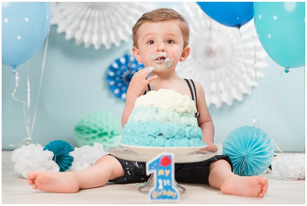 Cette image montre une séance photo Smash the Cake près d'Evreux, dans le studio d'un photographe. Un fond de studio bleu a été tendu et décoré avec des rosaces en papier et des ballons. Un enfant mange son gâteau de premier anniversaire. Le gâteau est recouvert de crème fouettée bleue.
