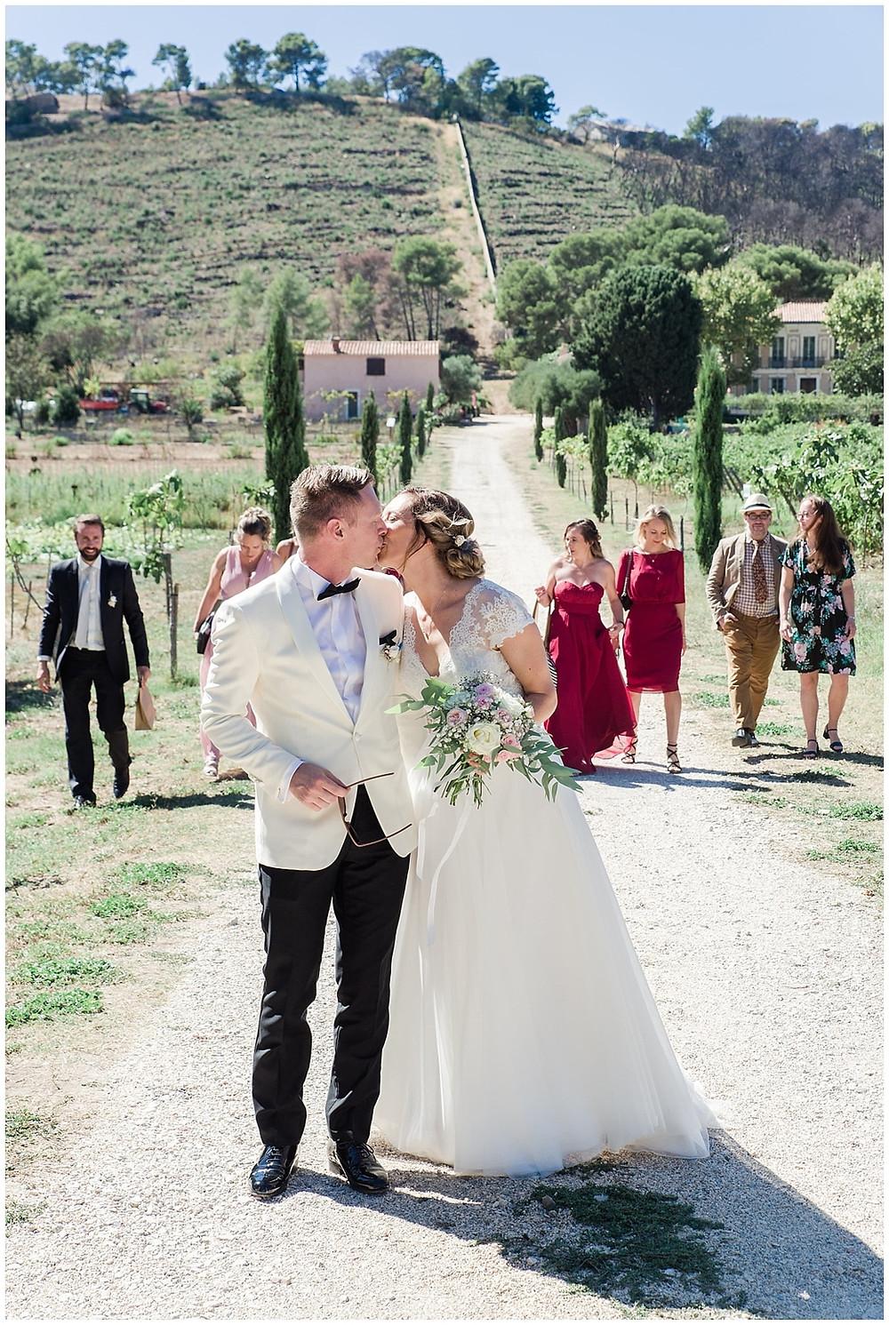 Le marié et la mariée se dirigent vers le lieu de cérémonie, à Saint-Mandrier-sur-mer, dans le Var. Ils marchent sur un chemin de terre battue et s'embrassent, suivis par leurs demoiselles et garçons d'honneur. La mariée porte un bouquet blanc et rose.