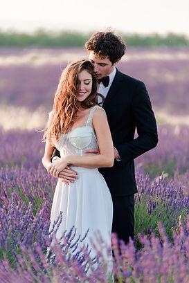 Couple de mariés enlassés en robe et costume dans les champs de lavandes au crépuscule après leur mariage à Saint-Lô dans la Manche