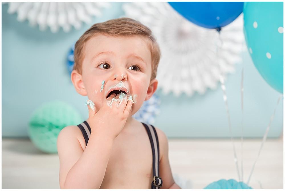 L'enfant mange la crème fouettée lors de sa séance photo smash the cake au studio life stories dans l'eure.