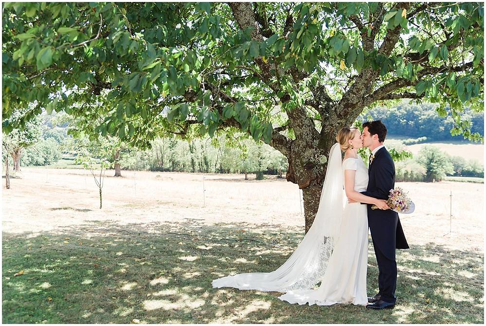 Lors d'un mariage en Bourgogne, les mariés s'embrassent à l'ombre d'un arbre. Le marié porte une costume queue de pied bleu marine, la mariée porte une robe longue blanche et fluide ainsi qu'un voile avec de la dentelle.