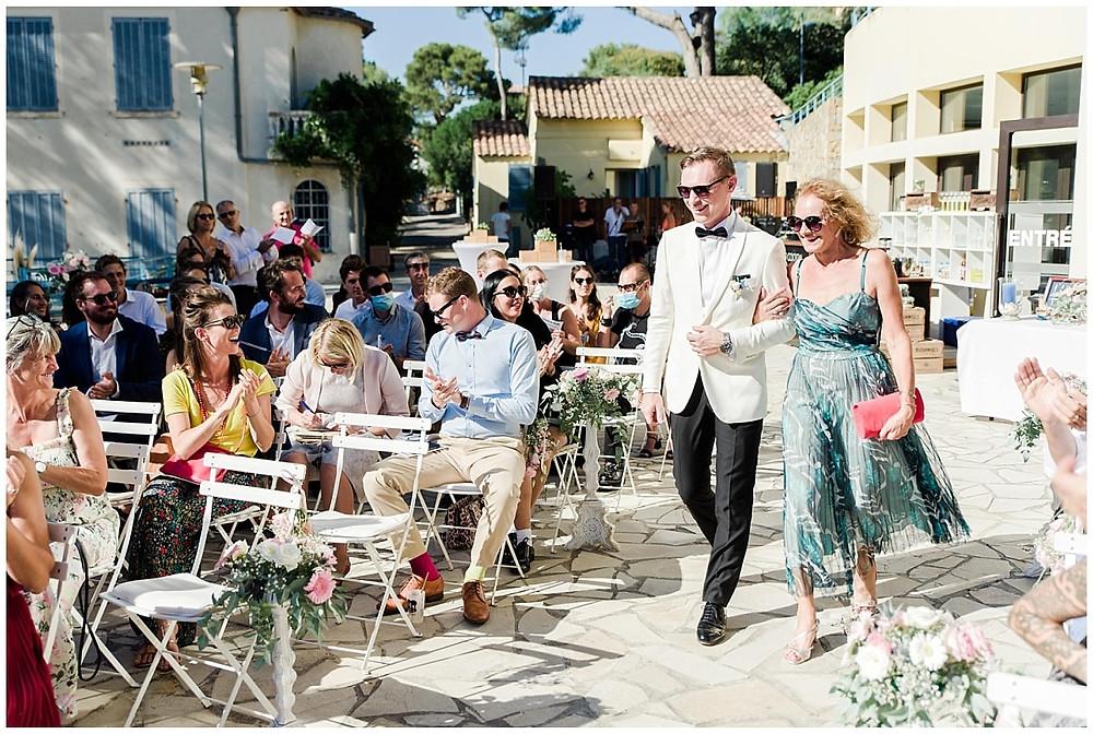 le marié arrive au bras de sa mère pour la cérémonie laïque de mariage à Saint-Mandrier-sur-Mer dans le var. Les invités applaudissent. La cérémonie se passe sur une terrasse avec vue sur la mer.