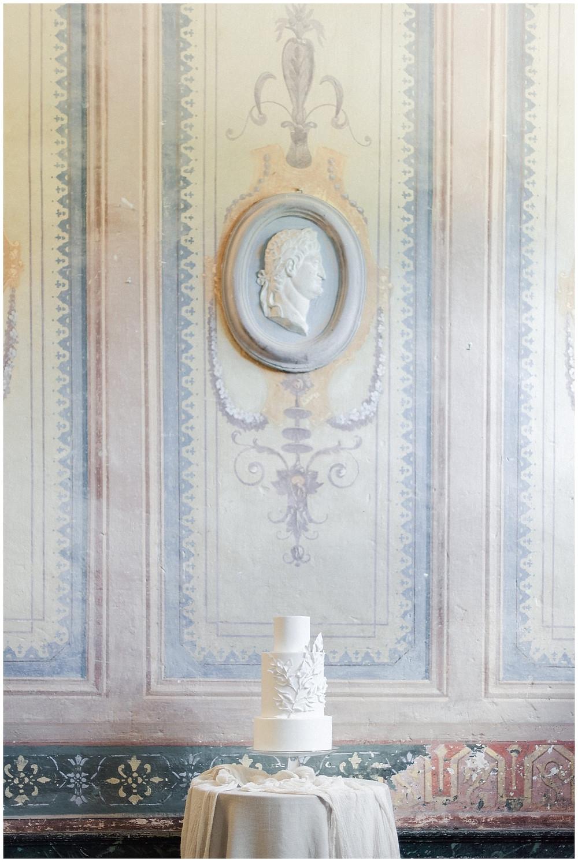 Photo du wedding cake : mariage au Château de Sénéguier en Provence. Il s'agit d'un wedding cake entièrement blanc, placé sur une table haute nappée. Le wedding cake est décoré de motifs floraux élégants, blancs également. Le wedding cake est placé dans l'entrée du château, devant les magnifiques peintures du 17ème siècle.
