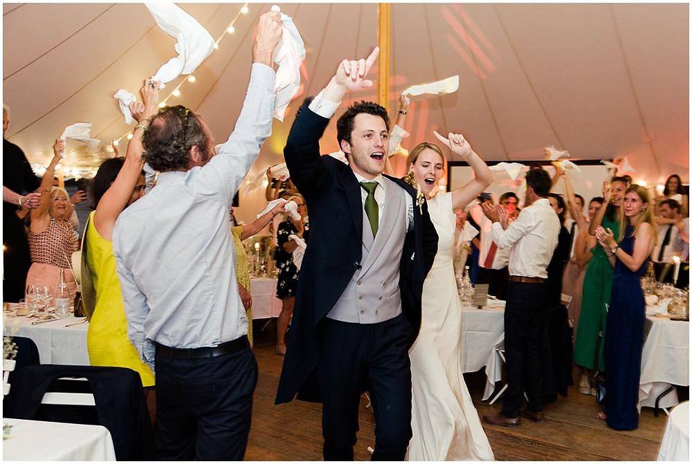 Sur cette photo, on peut voir l'entrée festive des mariés sous la tente sous laquelle se déroule leur dîner de mariage. Ils sont très joyeux, les invités font tourner leurs serviettes.