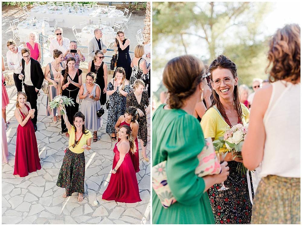 Une des invitées a attrapé le bouquet et le montre à la mariée, folle de joie.