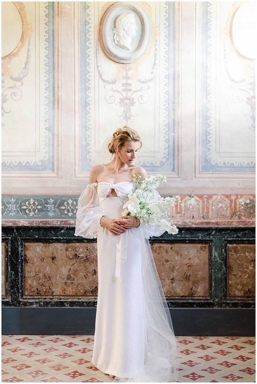 Portrait de mariée au Château Sénéguier en Provence. La mariée se tient debout dans l'entrée du château, devant les peintures murales d'époque. Elle porte une robe fluide, avec des manches bouffantes. Son bouquet est destructuré et blanc. Elle porte un voile et son chignon est très moderne.