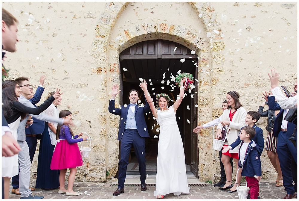 Sur cette image, on peut voir une sortie d'église des mariés, à la fin de la cérémonie de mariage. Les mariés sortent par la grande porte, les invités jettent des pétales de roses. Les mariés sont très joyeux.