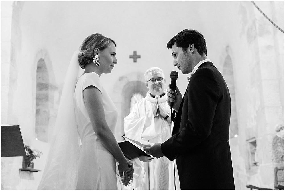 Sur cette photo, on peut voir les mariés échanger leurs vœux lors de leur cérémonie religieuse de mariage dans une petite église d'un village en Bourgogne. Les mariés se regardent, lisent leurs vœux et le prêtre les regarde aussi, attendri.