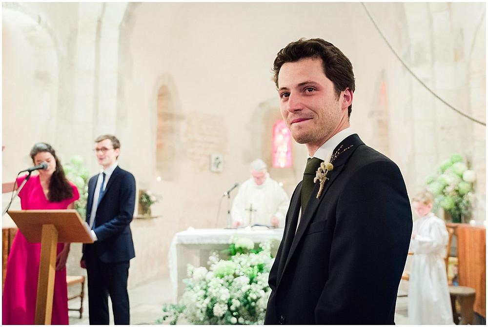 Le marié est très ému de voir la mariée arriver au bras de son père à l'église lors de la cérémonie religieuse de mariage à l'église dans un petit village de Bourgogne.