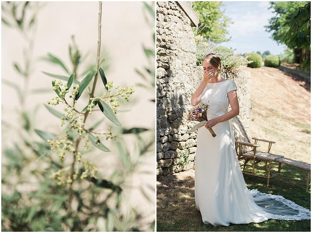 La mariée est très émue de ce moment de découverte des mariés : elle pleure.  Cette scène a été prise sous des arbres en Bourgogne en été. La mariée porte une robe longue et épurée, ainsi qu'un voile avec de la dentelle.