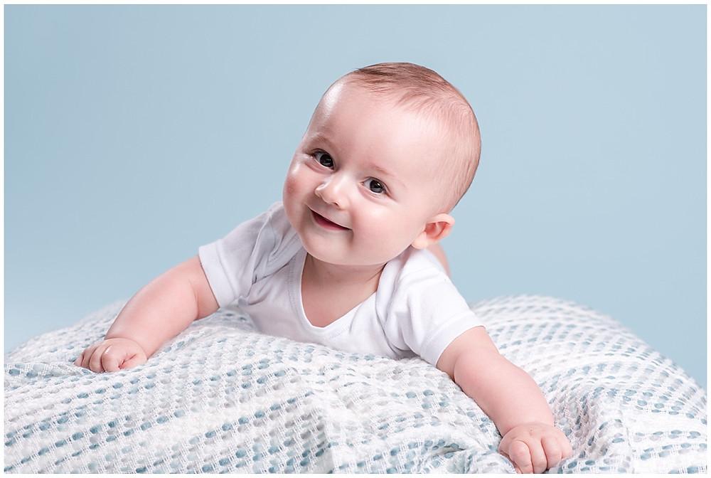 Portrait d'un bébé lors d'une séance photo bébé de 6 mois au studio life stories situé prés de Louviers. Le bébé est allongé sur le ventre et il sourit. Le fond photo est bleu clair.