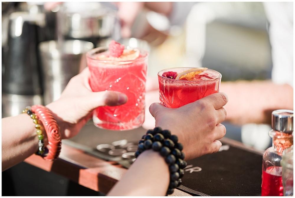 Une invité prend deux cocktails dans ses mains, lors du cocktail à la suite de la cérémonie laïque.