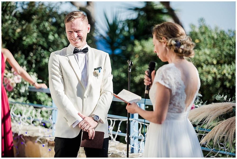 Le marié sourit et rit en écoutant les vœux de sa femme lors de la cérémonie de mariage.