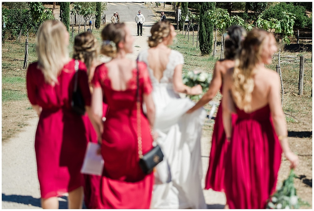 Le marié aperçoit de loin la mariée qui arrive pour le first look, accompagnée de ses demoiselles d'honneur toutes vêtues de rouge. Les jeunes filles marchent sur un chemin en terre battue, le marié se trouve au bout de ce chemin, vêtu de son smoking.