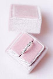 Boite à alliance en velours rose pâle sur fond rose poudré contenant une aliance tour de diamants en or blanc
