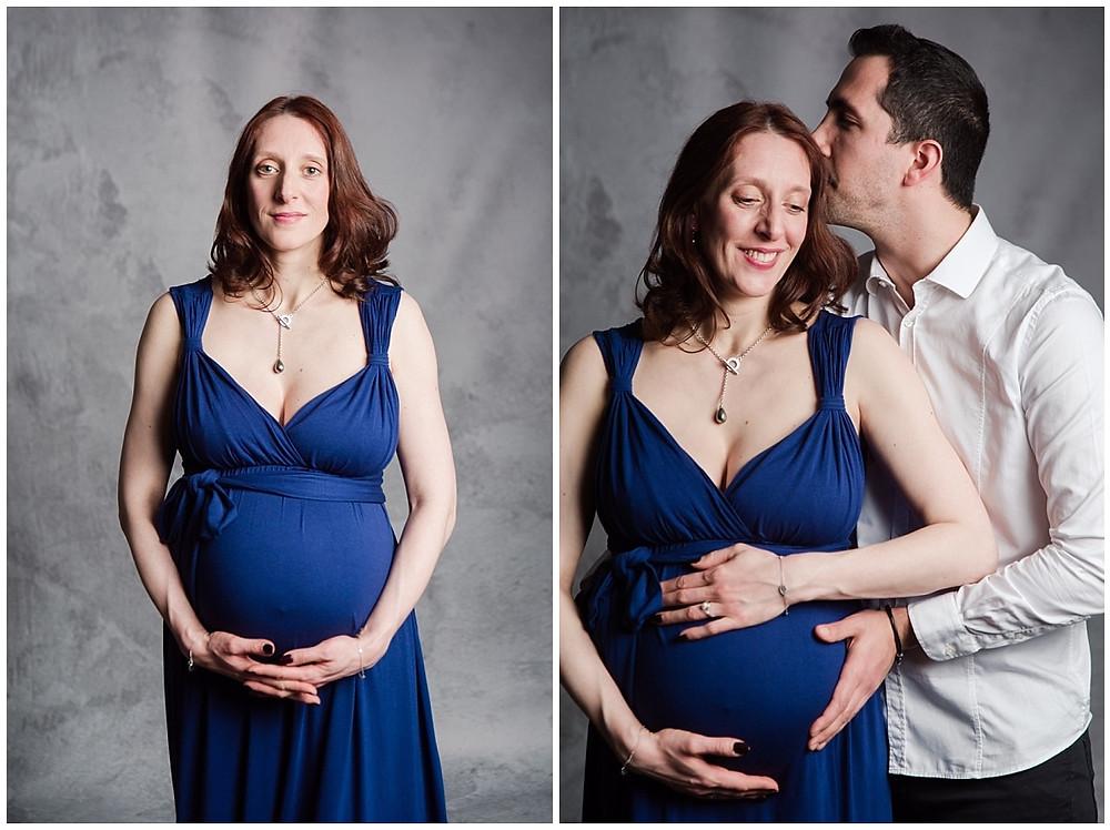 Portrait des deux futurs parents lors d'une séance photo grossesse au Studio Life Stories, studio photo situé près de Louviers. La future maman et le futur papa sont très proches l'un de l'autre, le futur papa embrasse le front de la future maman. Ils caressent le ventre de femme enceinte tous les deux. La future maman porte une robe bleue longue et le future papa une chemise blanche et un pantalon noir.