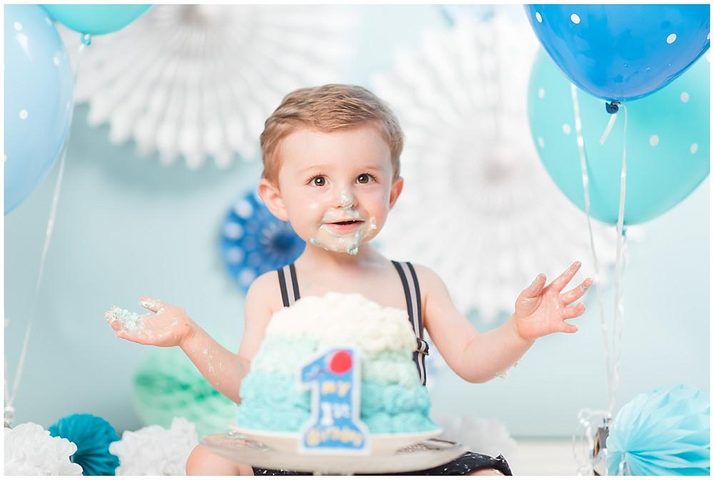 Photo d'un enfant de un an lors d'une séance photo Smash the Cake dans un studio chez un photographe professionnel près d'Evreux. L'enfant est placé sur un fond bleu ciel, il y a un décor de ballons et de rosaces en papier. Devant lui se trouve son gâteau d'anniversaire plein de crème fouettée bleue, assortie au fond photo. Il y a aussi une grosse bougie pour son premier anniversaire. L'enfant est joyeuse et mange son gâteau. Il a de la crème fouettée sur les mains et sur le visage.