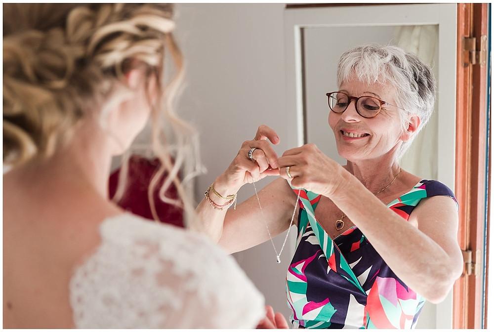 Au moment de l'habillage de la mariée, la mère de celle-ci lui passe les bijoux. Elle lui accroche un collier.