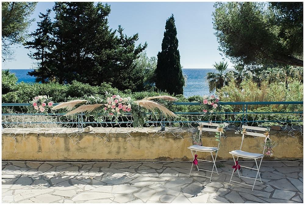 Magnifique lieu de cérémonie laïque à Saint-Mandrier-sur-Mer : sur une terrasse avec vue sur la mer. La terrasse a été décorée par la fleuriste à l'aide de fleurs roses et blanches et d'herbes de pampa. Les deux chaises des mariés sont aussi décorées de fleurs fraiches.