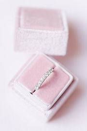 paris wedding photographer - Pale pink velvet wedding ring box on a powder pink background containing a ring of diamonds wedding ring in white gold next to Paris in France