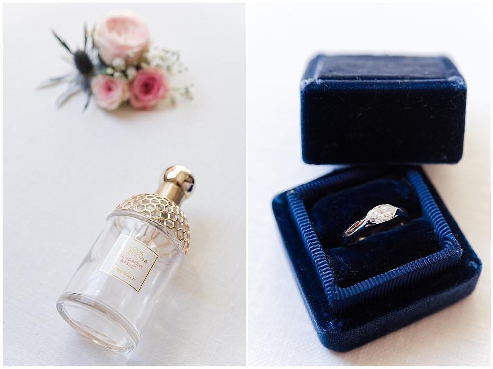 Mise en scène des accessoires de la mariée : son parfum de Guerlain est posé au premier plan, de jolies fleurs assorties au mariage sont floues au deuxième plan. A côté, on peut voit un zoom sur la bague de fiançailles en diamant.