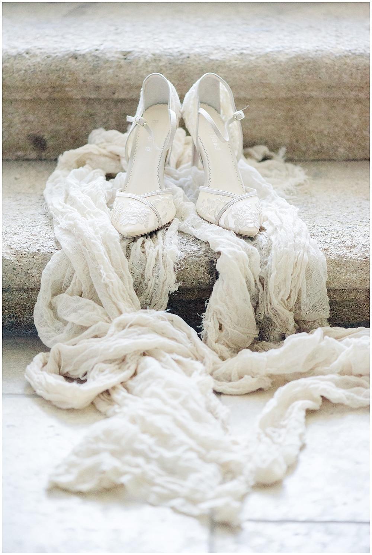 Photos des chaussures de la mariée au Château de Sénéguier : les chaussures sont élégantes, en dentelle, à bout pointu, avec un talon moyen. Elles sont posées sur les marches en pierre du château.