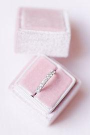 Photographe mariage tarn - Boite à alliance en velours rose pâle sur fond rose poudré contenant une aliance tour de diamants en or blanc près d'Albi dans le Tarn