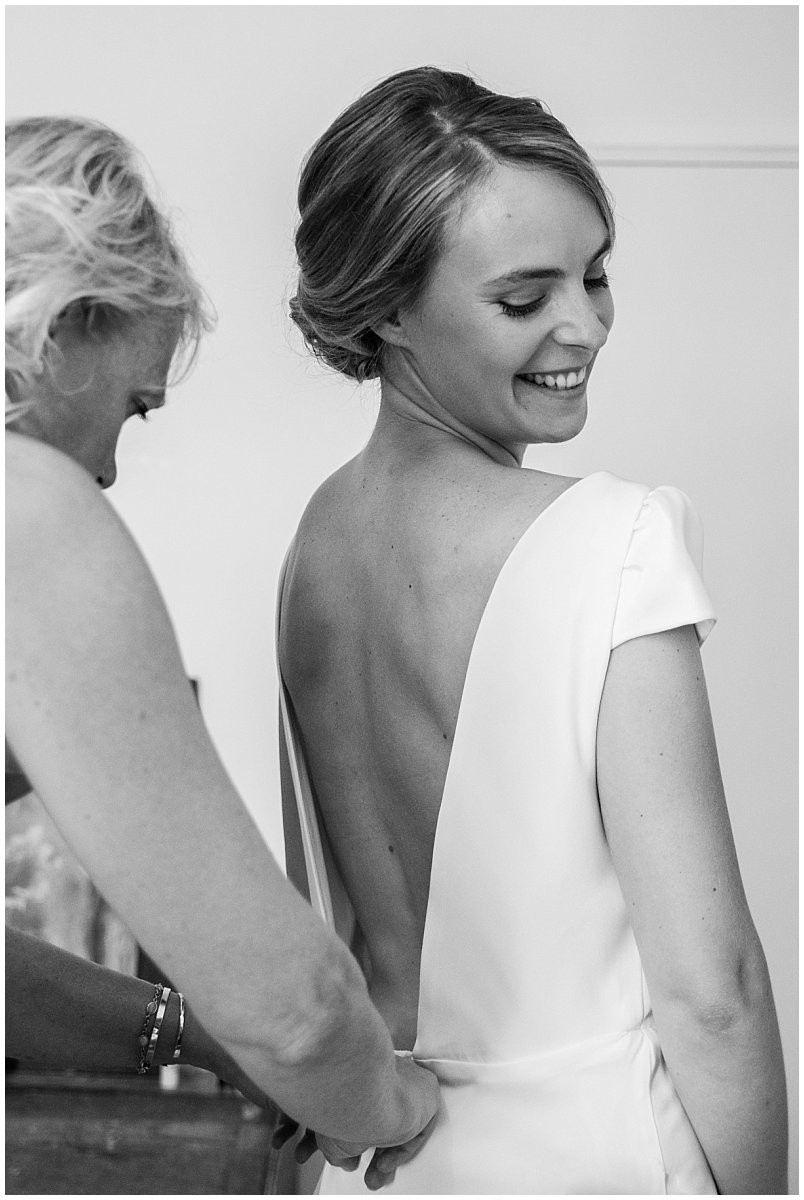 La mère de la mariée aide sa fille à fermer sa robe.