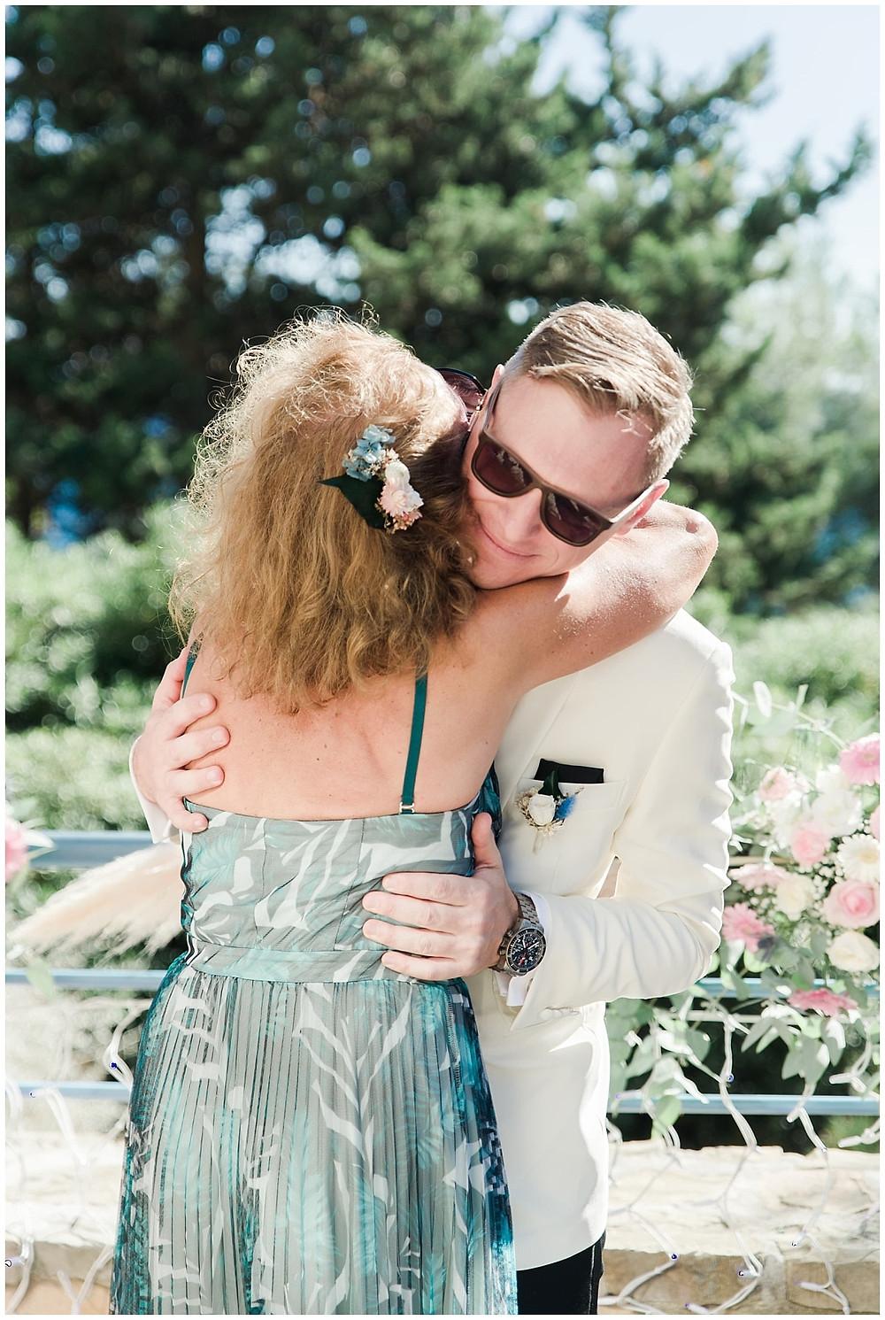 Le marié enlace sa mère alors que la cérémonie laïque de mariage va commencer.
