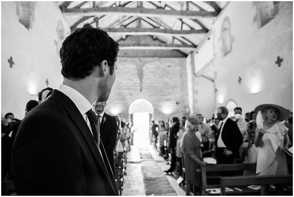Le marié attend sa future femme devant l'autel lors de la cérémonie religieuse dans une petite église de Bourgogne.