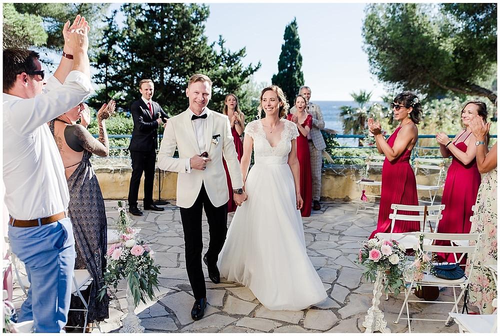 Sortie de cérémonie pour les mariés : ils remontent l'allée du lieu de cérémonie, applaudis par leurs invités. On peut voir beaucoup de joie sur cette image.
