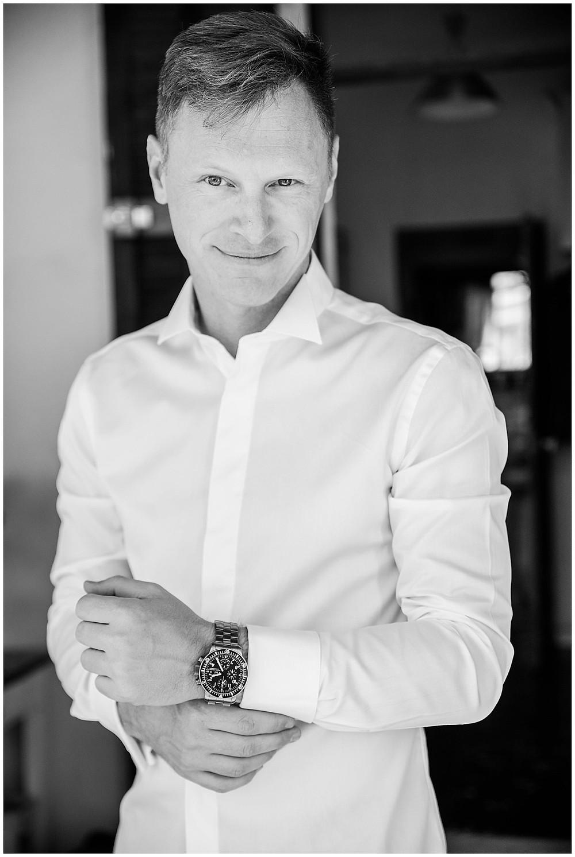 Portrait du marié en noir et blanc en train de se préparer : il a enfilé sa chemise, il est en train de fermer sa montre.