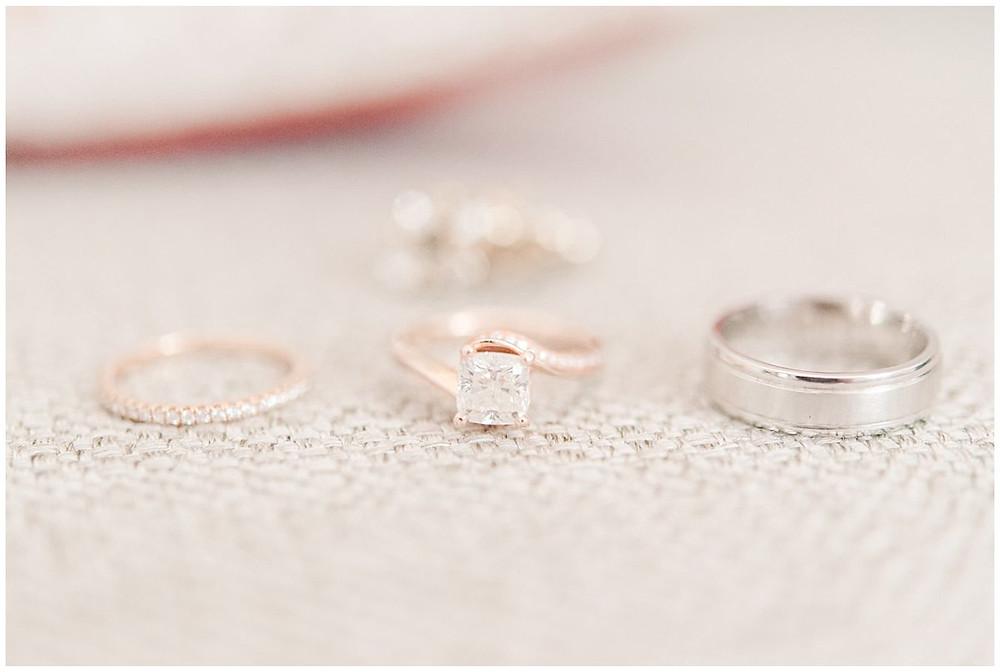 Sur cette image, on peut voir 3 bagues de mariage. Il y a la bague de fiançailles en diamants et les deux alliances des deux mariés. Les trois bagues sont alignées et posées sur un tissus beige.