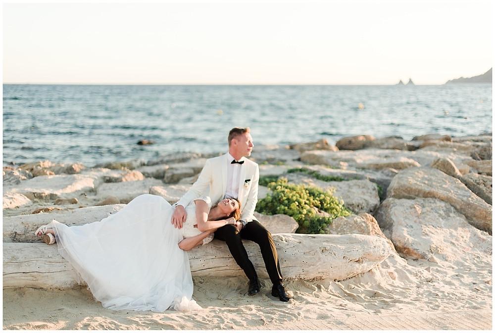 Moment romantique lors de la séance photo de couple mariage à Saint-Mandrier-sur-mer : les mariés sont assis sur la plage, au coucher du soleil.