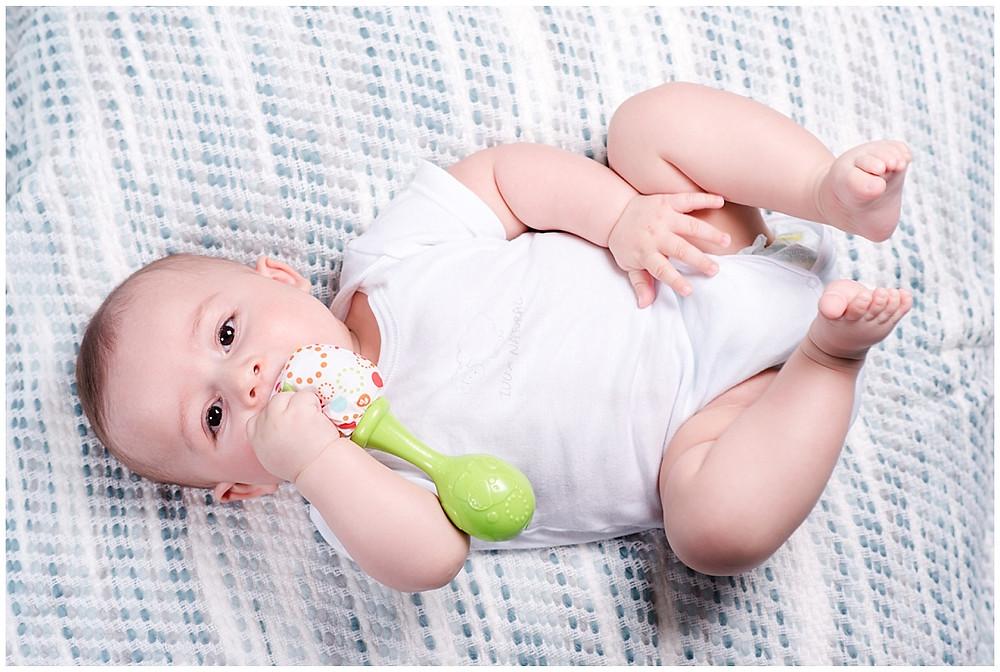 Le bébé est en train de jouer avec son hochet lors d'une séance photo bébé 6 mois au studio life stories. Il est allongé sur une couverture bleu et il est en body.