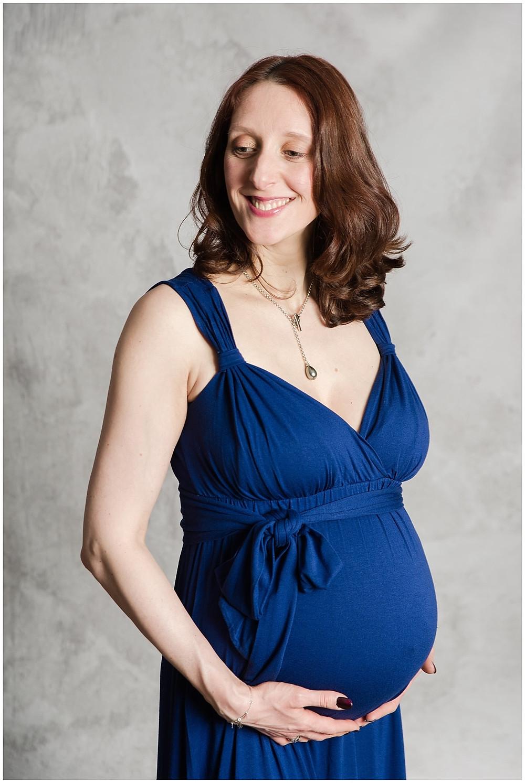 Portrait d'une femme enceinte au Studio Life Stories, studio photo près de Louviers. La jeune femme est enceinte de 8 mois et porte une robe longue bleue. Le fond est gris, la jeune femme enceinte est rousse et elle porte un collier. Elle sourit et semble radieuse de vivre sa grossesse.
