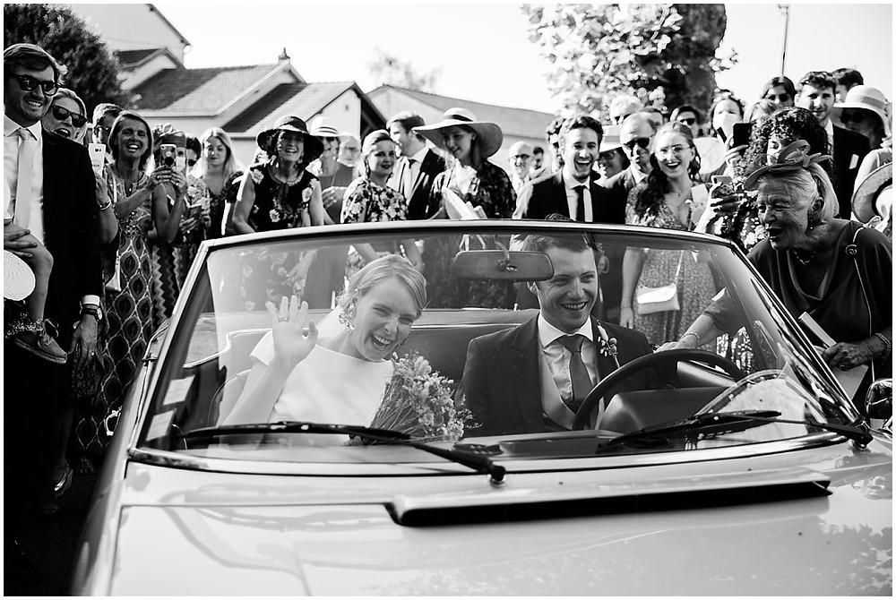 Sur cette photo, on peut voir les mariés quitter l'église d'un petit village en Bourgogne où a eu lieu leur cérémonie religieuse de mariage. Ils quittent le lieu dans une superbe voiture de collection, acclamés par leurs proches.