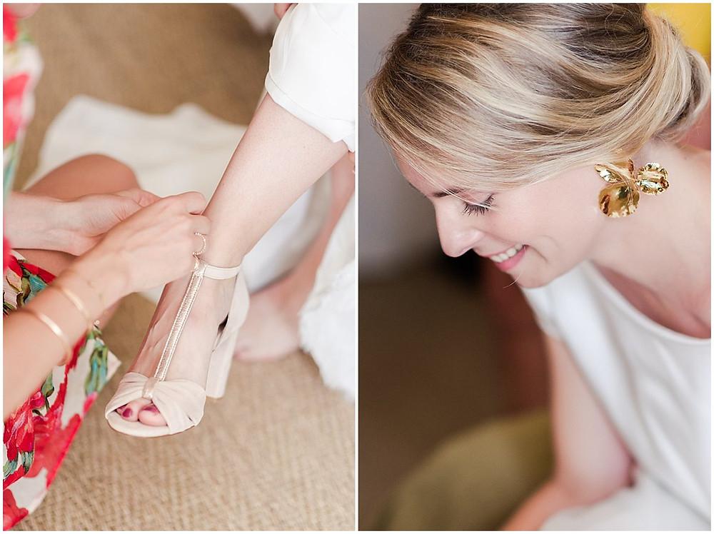A la fin de son habillage, la mariée enfile ses chaussures. Elle est aidée par sa soeur qui ferme la bouche de ses chaussures. Ses chaussures sont des chaussures ouvertes à talon, aux jolis tons beige-rosé.
