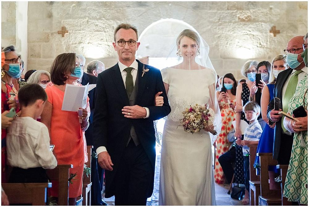 La mariée fait son entrée dans l'église au bras de son père.