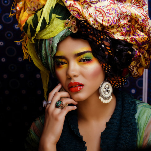 Fashion editorial photography: Portrait of cuban model with creative makeup and a floral head piece.