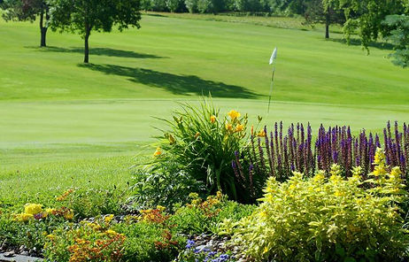 Gorgeous flowers behind the green of a stunning par four.