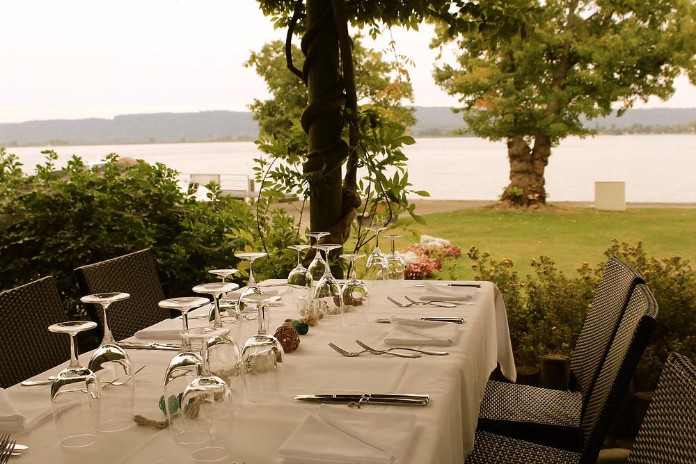 Gedeckter Tisch auf Terrasse mit Blick auf See