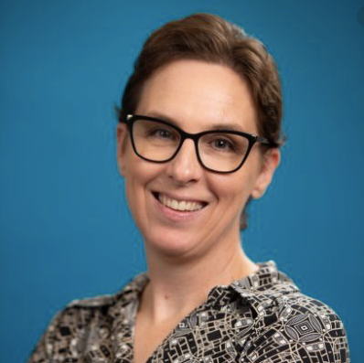 Photo of Kathy wearing black glasses, smiling. She has light brown hair and pale skin.