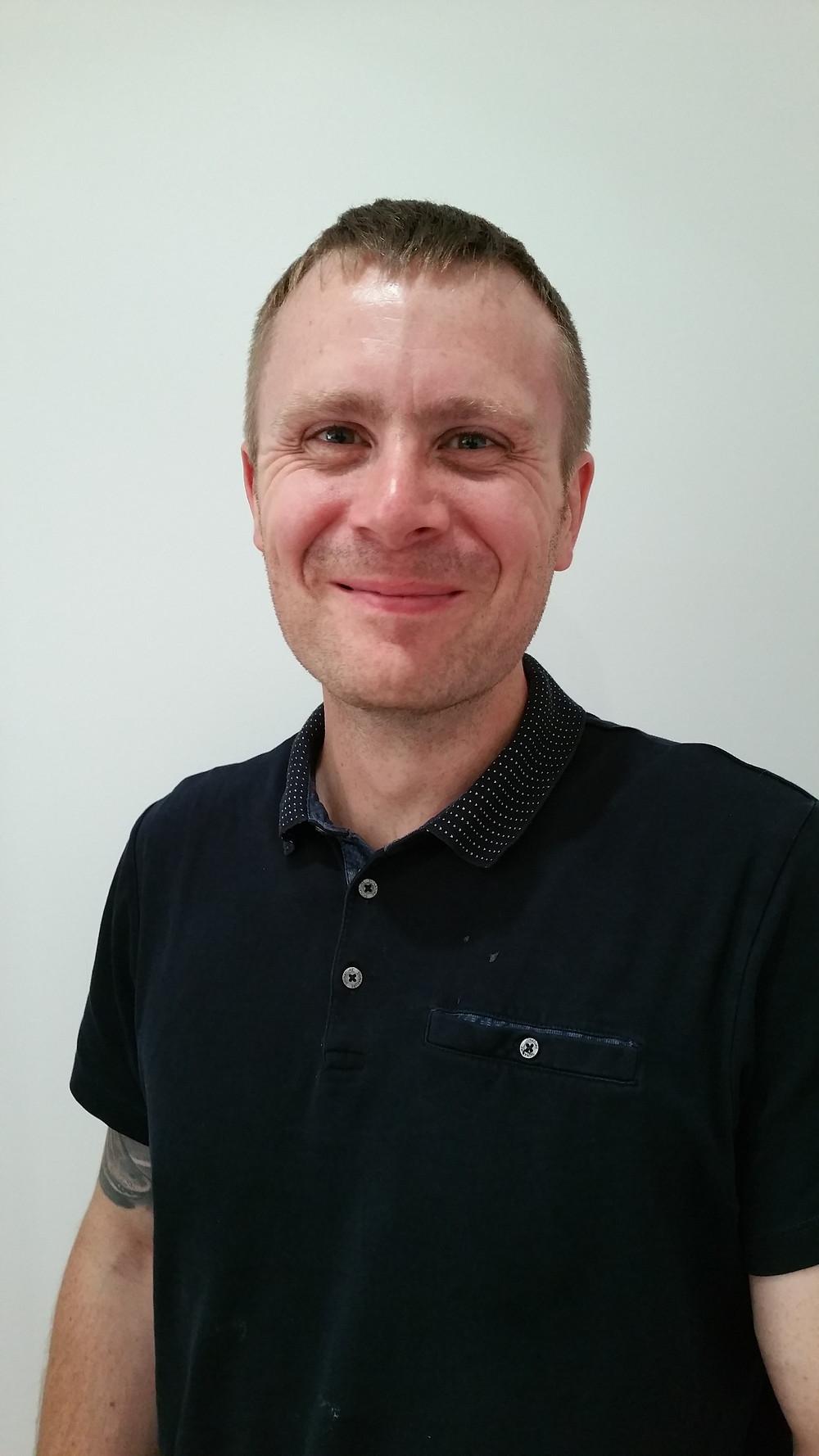 Photo of Dan smiling. Dan is wearing a black shirt and has short hair.